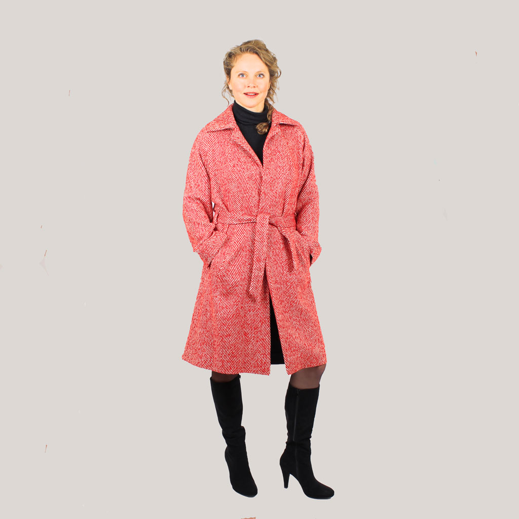 Model volledig in beeld in Roadcoat, rode lange jas